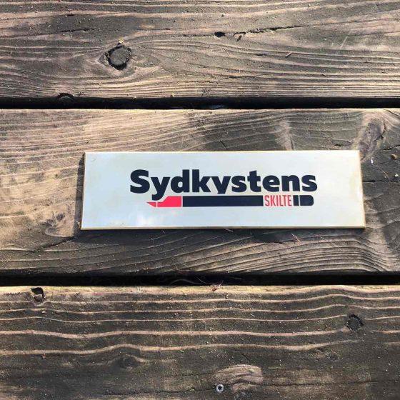 Ægte dybdegraverede messingskilte, farvelagt med lak. Messingskilte anvendes typisk som dørskilte eller firma/facadeskiltning. Vi leverer til døren.
